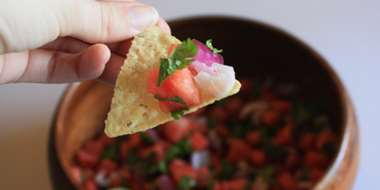 woman holding chip with watermelon salsa in a bowl